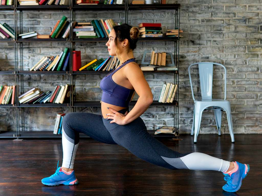 woman dooing a lunge stretch insider her home