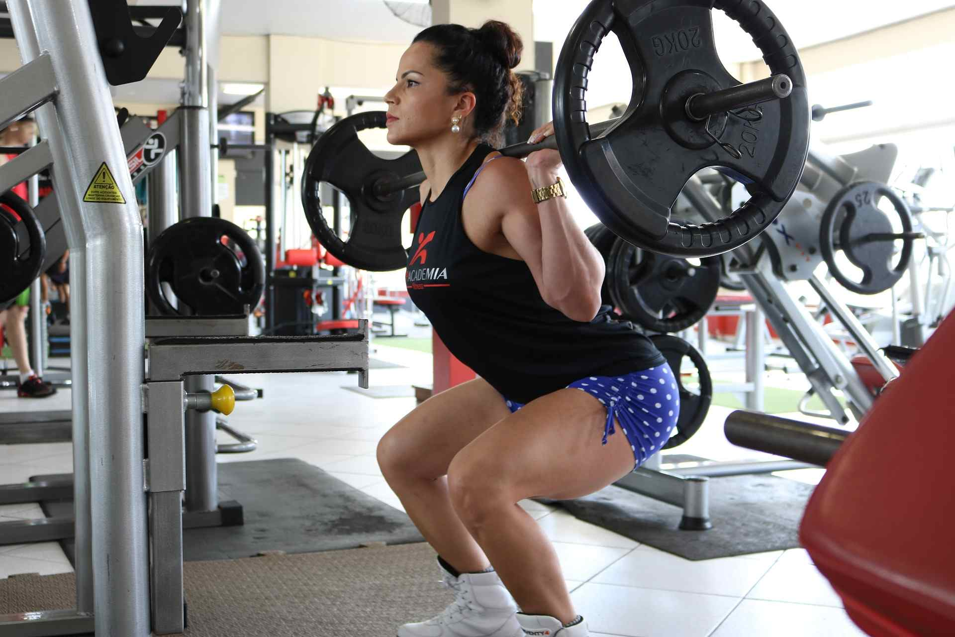 woman weight training doing squats with barbell on shoulders