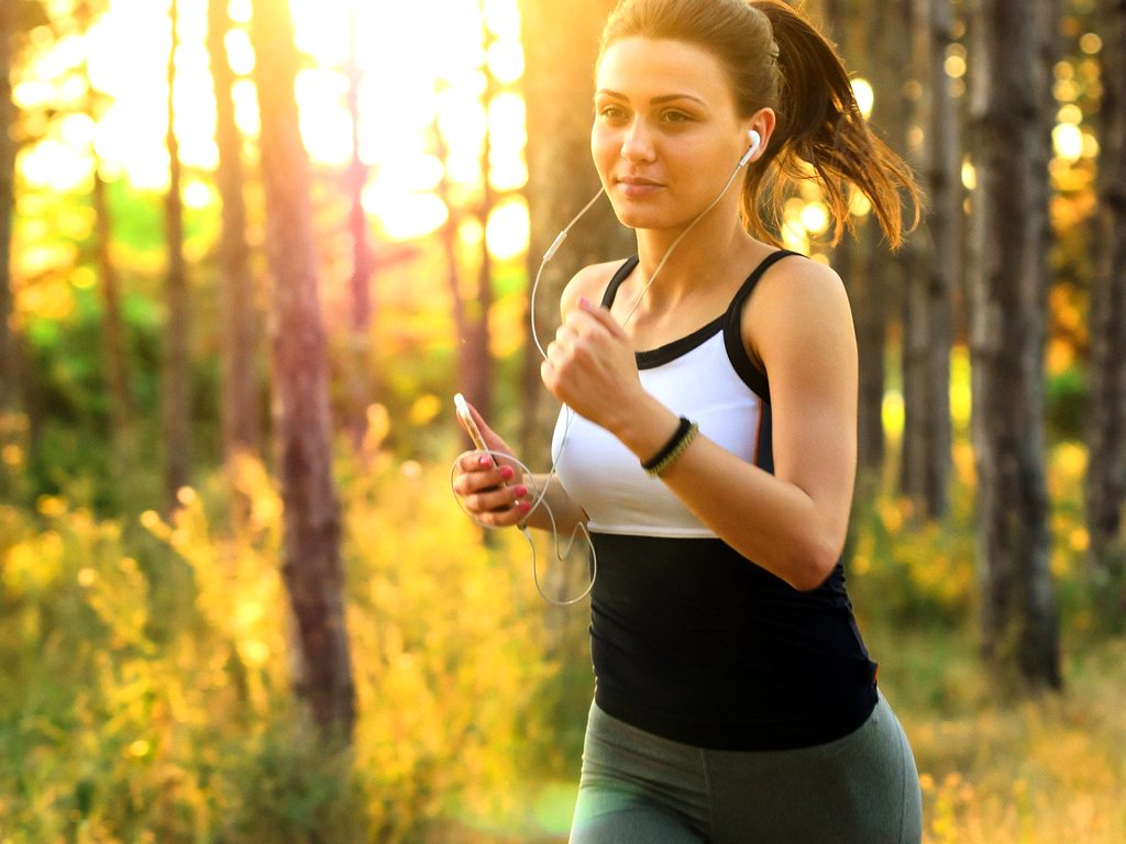 woman with ear buds, jogging in a forest